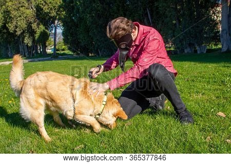 Boy Wearing Old Style Virus Mask   With His Dog Playing At Garden