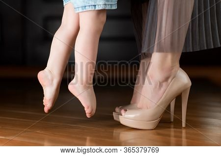 A Little Girl With Bare Feet Reaches For A Shod Mom In The Hallway At Home. Mom Takes The Baby And T