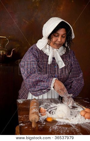 Vintage scene of a colonial woman kneading dough in an antique kitchen