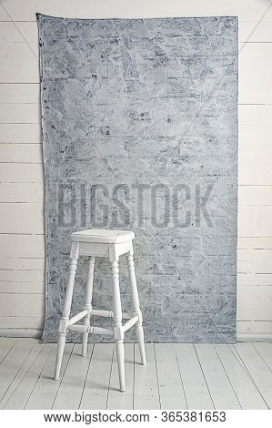 White High Wooden Stool With A Grey Textured Background. Bar Chair In White Wooden Minimalist Room.
