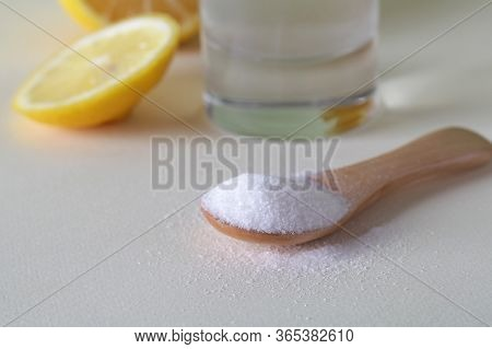 Powdered Vitamin C On Wooden Spoon With Glass Of Water And Cut Lemon On White Background Close Up
