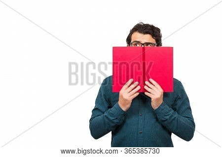 Student Guy Hiding Behind A Red Book, Looking Suspicious Aside Isolated On White Background With Cop