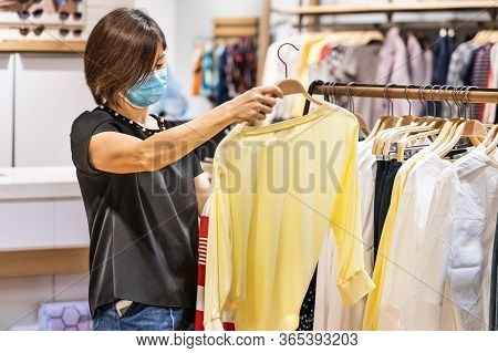 Asian Woman Shopping Apparels In Clothing Boutique With Protective Face Mask As New Normal Requireme