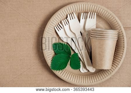 Wooden Forks And Paper Cups With Plates On Kraft Paper Background. Eco Friendly Disposable Tableware