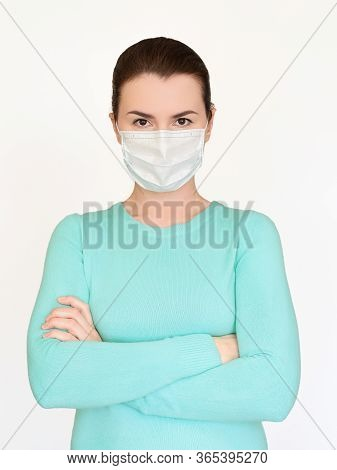 A Young Woman In A Medical Mask Hands Crossed On Her Chest. Concept Of Discontent, Pandemic Time, Vi