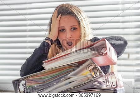 Face Of Office Worker Is Distressed With A Lot Of Paperwork In Front Of Her. A Lot Of Paper Work In