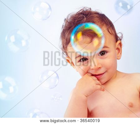 Closeup portrait of naked nice little kid isolated on blue background, cute happy baby boy bathe, adorable child with finger in mouth, sweet infant play with soap-bubble, healthy childhood