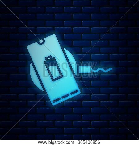 Glowing Neon Smartphone Charging On Wireless Charger Icon Isolated On Brick Wall Background. Chargin