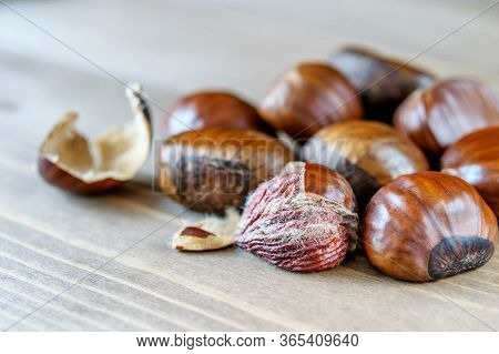 Heap Of Big Ripe Chestnuts On The Wooden Background Closeup. Healthy Sweet Fruit Chestnut, Macro.