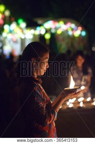 Chiang Mai, Thailand - November 9, 2019: Asian Girl Light The Candle To Pray In Loi Krathong Festiva