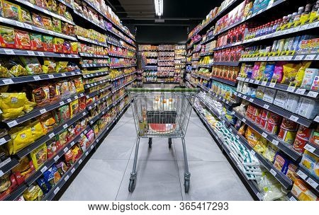 Shopping Cart Trolley With A Product On Shelves At Aisle Of Grocery Store Supermarket