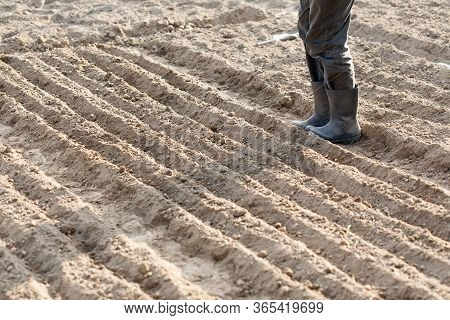 Boots On The End Of Land Prepared For Planting