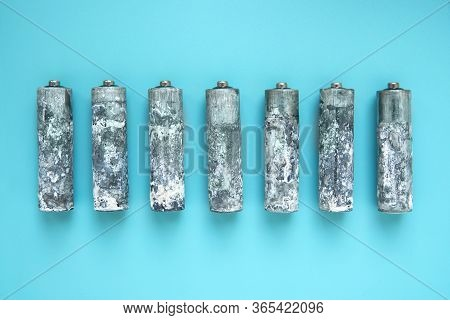 Seven Heavily Oxidized Aa Batteries Unwrapped And Laid Out In A Row On A Blue Background.