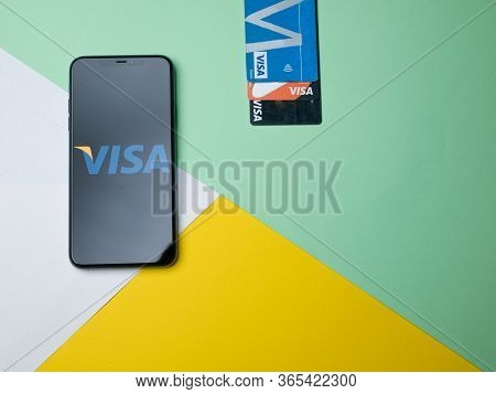 Usa - May, 2020 Visa App On Iphone Screen With Plastic Banking Cards On Colored Background. Visa Is