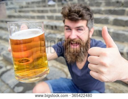 Man With Beard And Mustache Holds Glass With Beer And Shows Thumb Up, Stone Stairs Background. Hipst