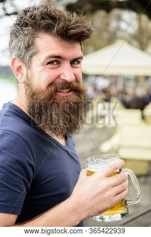 Man With Beard And Mustache Holds Glass With Beer While Relaxing At Cafe Terrace. Happy Smiling Youn