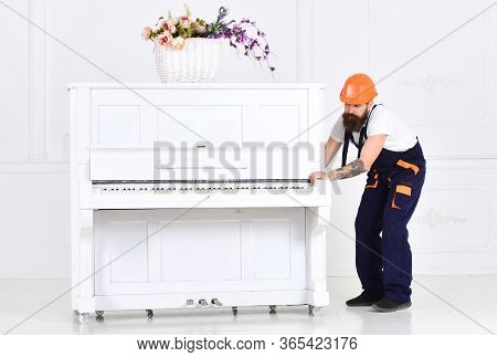 Busy Worker In Orange Protective Helmet And Blue Overall Moving Grand Piano Isolated On White Backgr