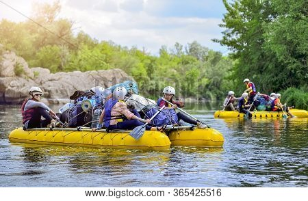 A Group Of People Rafting On A Stormy River In The Yellow Rafts Fully Loaded With Personal Belonging