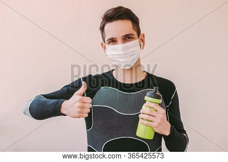 Happy Man Fitness Instructor In Medical Face Mask Showing Thumb Up Gesture. Young Confident Sports M
