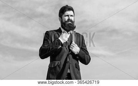Serious Hipster. Charismatic Male. Businessman Against The Sky. Brutal Caucasian Hipster With Mousta