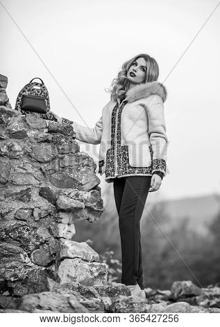 Wardrobe For Cold Weather. Girl Stand Near Stone Ruins. Fancy Chic Coat. Natural Wool Sheepskin Coat