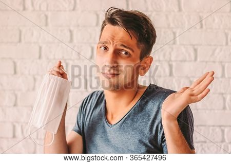 Portrait Of Confused Man With Funny Sun Tan Lines On Face Holding Protective Mask In Hand. Young Hip