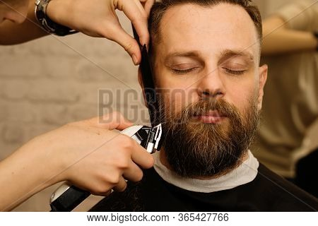 Barber Trimming Beard Of Male Customer With Electric Razor At Barbershop. Man With Beard And Moustac