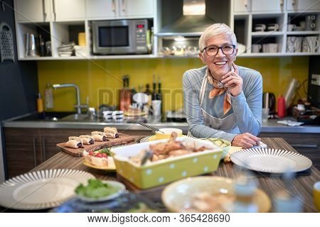 satisfied grandma waiting guests with ready food on a table.