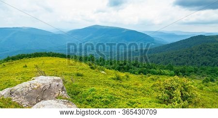Beautiful Summer Landscape In Mountains. Green Grassy Meadow On The Hill Side. View In To The Distan