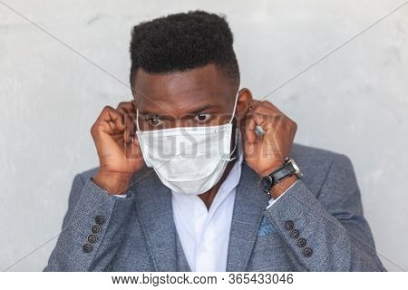Covid-19. Young African Man Puts On A Protective Medical Face Mask To Prevent Infection With Coronav