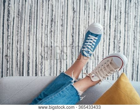 Relaxing Teenager's Feet In Different Colors Beige And Blue Casual New Sneakers On Cozy Comfortable