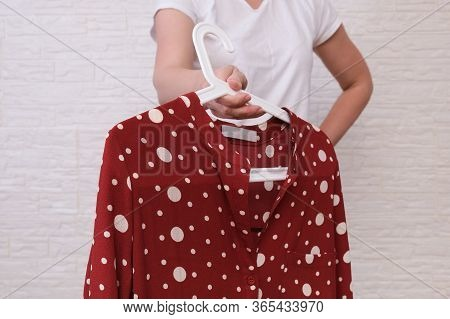 Caucasian Woman Choosing Clothes, She Is Holding A Hanger With Fashionable Blouse, Shopping, Fitting