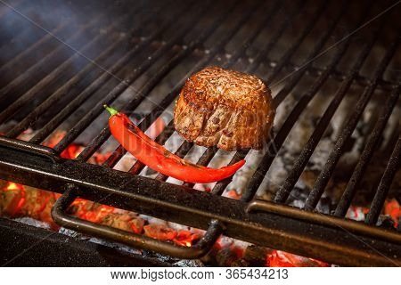 Grilled Beef Steak With Red Pepper On Grill, Side View.