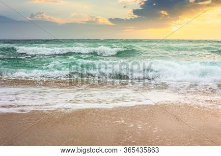 Storm On The Sandy Beach At Sunrise. Dramatic Ocean Scenery With Cloudy Sky. Rough Water And Crashin