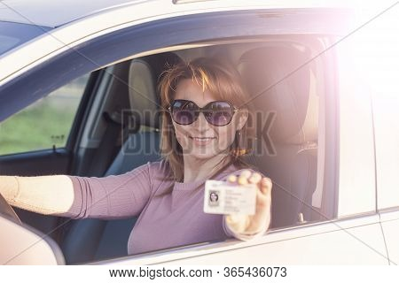 Obtaining A Driver's License, A Beautiful Woman In Sunglasses At The Wheel Demonstrates A New Driver