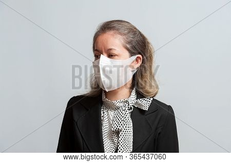 Front View Of Middle Aged Mixed Race Woman In Formal Wear Wearing White Surgical Mask For Protection