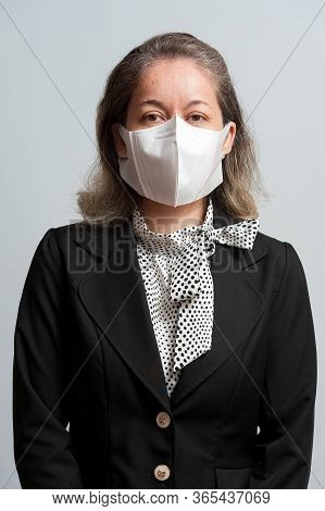 Side View Of Middle Aged Mixed Race Woman In Formal Wear Wearing White Surgical Mask For Protection