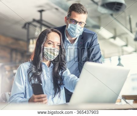 Good Looking Female And Male Coworkers Look At The Computer Screen Together, Wearing Face Masks.