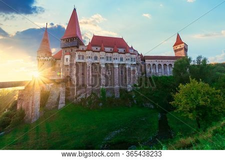 Legendary Corvins Castle In Hunedoara At Sunrise. One Of The Largest In Europe And Is In A List Of S