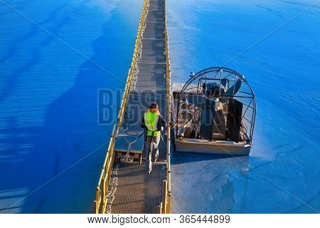 man walking on the bridge, airboat stationed by the bridge on the lake swamp