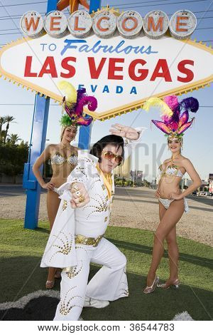 Elvis impersonator with casino dancers in front of a sign