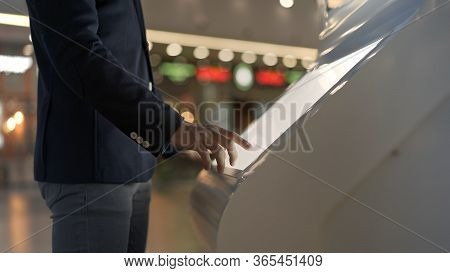 Young Businessman Hands Dressed In Jacket Swiping For Information In Kiosk On Background Of Lights O