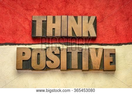 Think positive - word abstract in vintage letterpress wood type blocks against abstract paper landscape, optimism, positivity and mindset concept