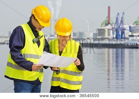 Two engineers, wearing safety gear, including goggles, hard hat, ear plugs and reflective safety vests, discussing blue prints in an industrial harbor with factories and plants in the background