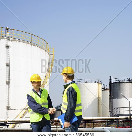 Two oil industry workers shaking hands in front of the storage tanks of a petrochemical refinary