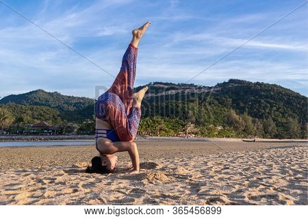 Asian Thai Woman Practicing Yoga At Evening In Mae Haad Beach, Koh Phangan Island, Thailand. Headsta