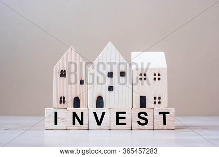 Invest Cube Blocks With Wooden House Model On Table Background. Coronavirus Pandemic, Business, Risk
