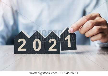 Young Businessman Hands Holding 2021 Happy New Year With House Model On Table Office. New House, Fin