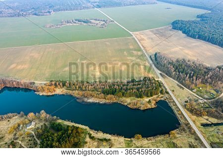 Picturesque Spring Landscape Of Countryside. Blue Lake, Green Fields And Forest On Horizon. Panorami