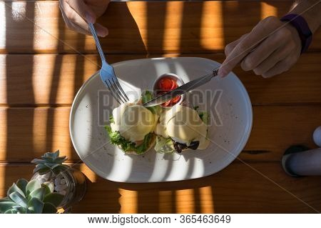 Person Eating Eggs Benedict With Hollandaise Sauce And Salmon Served With Halved Cherry Tomatoes. Ou